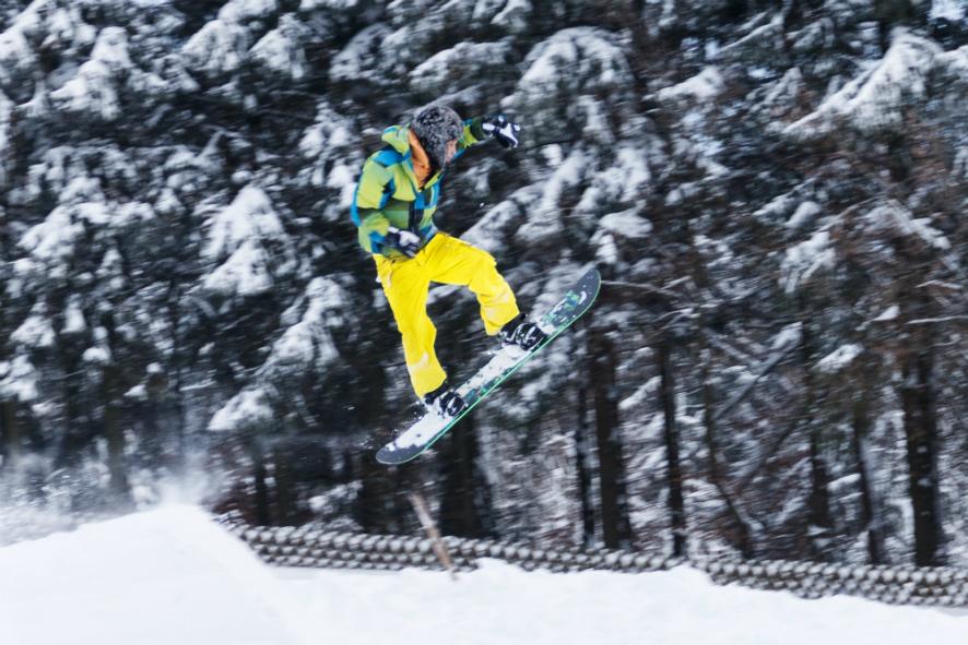 눈쌓인 나무들이 뒷쪽으로 보이고 스노우보드를 타는 사람이 높게 점프를 하고 있다.