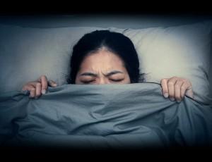 침대 속에서 여자가 인상을 찌푸리며 이불을 뒤집어 쓰고 있다.
