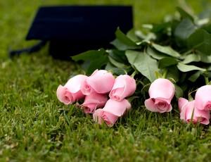 잔디 위에 분홍색 장미꽃 8송이와 학사모가 놓여있다.