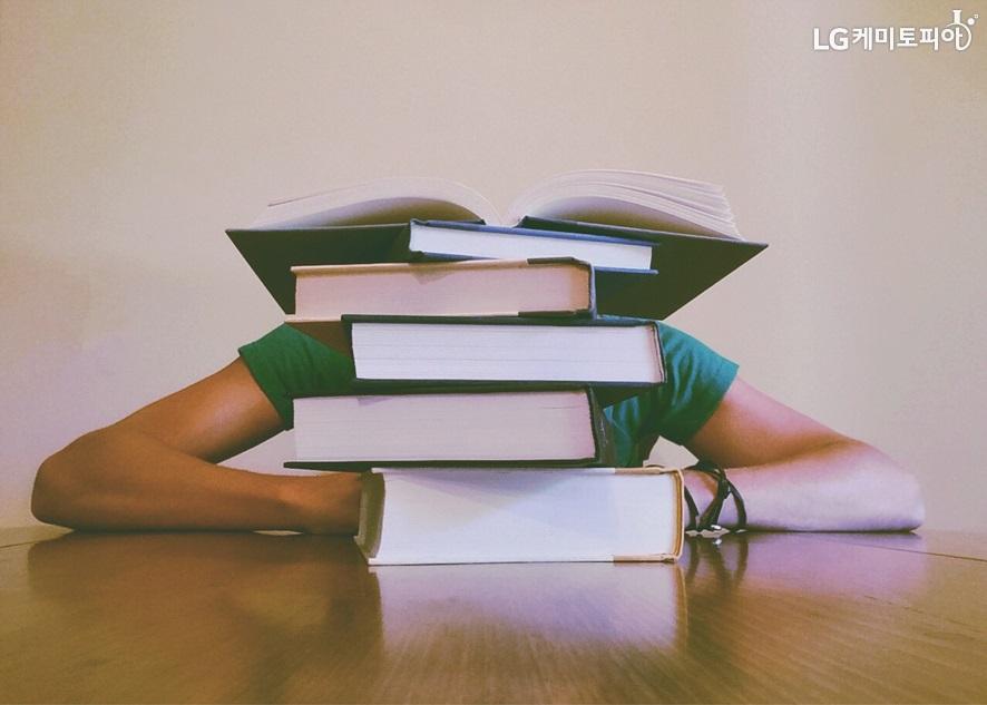 쌓여있는 책들 뒤에 엎드려있는 사람