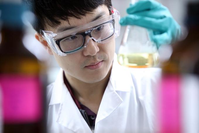 연구원이 연구용 고무장갑과 보호안경을 착용하고 실험을 하고 있다.