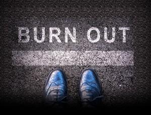 아스팔트 위에 Burn out이라고 써져있는 있고 그 앞에 남자 구두가 보인다.
