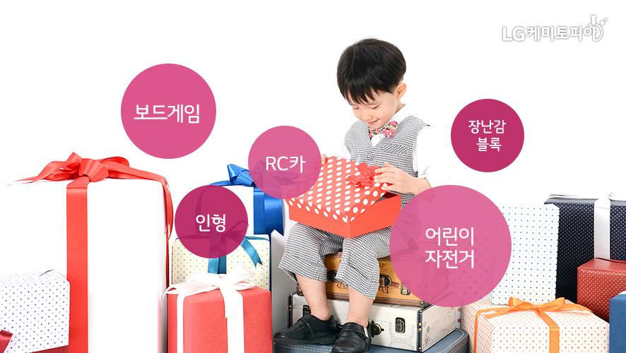 남자아이가 선물을 풀어보고 있는 사진. 어린이날 인기 선물로는 보드게임, 인형, RC카, 어린이 자전거, 장난감 블록