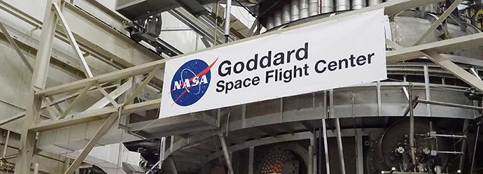 중장비 위로 Goddard Space Flight Center가 적힌 현수막이 걸려있는 사진이다.
