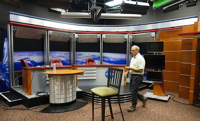 나사 TV 스튜디오 내부의 모습이다. 지구 모양의 벽지 앞으로 뉴스 진행을 위한 테이블과 의자들이 있다.