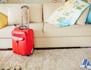 흰색 소파 위에 색색별 쿠션이 있고 그 옆에 세계지도가 펼쳐져 있다. 소파 앞쪽으로 베이지색 카펫이 깔려있고 그 위에 빨간색 플라스틱 캐리어가 있다.