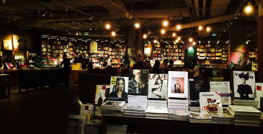 어두운 가운데 포인트 조명으로 멋을 낸 독립 서점 내부, 전방에 잡지들이 진열되어 있다.
