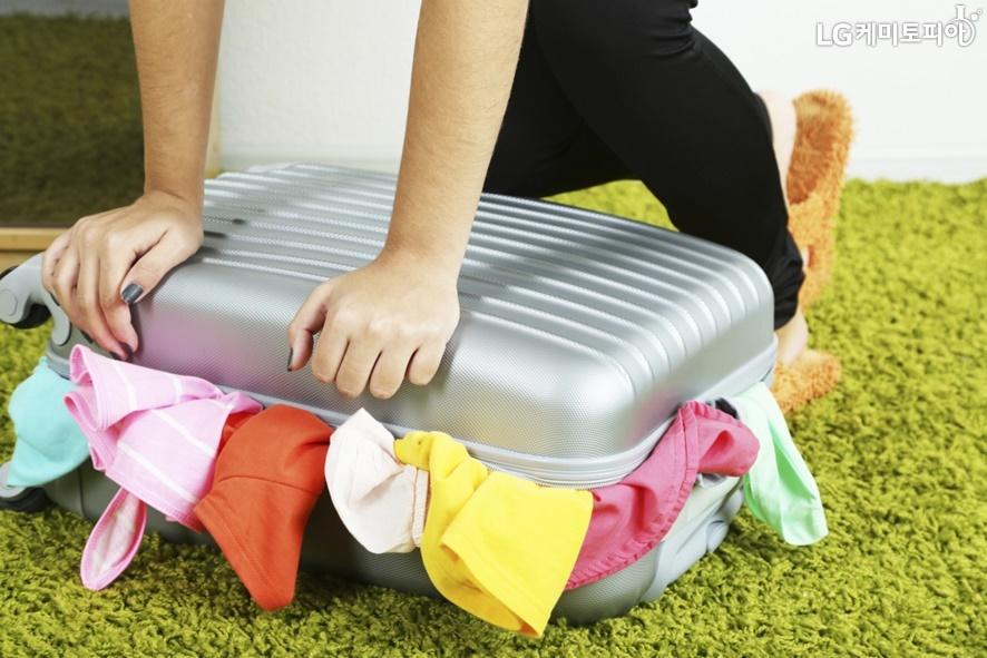 캐리어에 많은 옷가지들을 구겨넣고 닫히지 않는 것을 억지로 짓누르고 있는 모습.