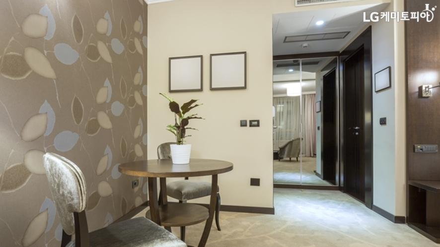 한 쪽 벽에만 어두운 갈색 포인트 벽지가 붙여진 거실 풍경