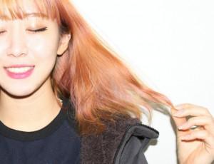 붉은빛도는 염색을 한 긴머리 여성이 머리카락 끝을 잡고 있다.