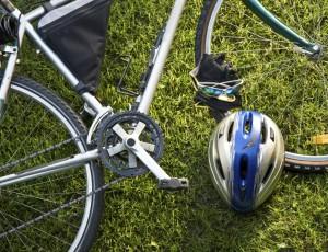 푸른 잔디 밭 위에 자전거 한대가 누워 있고 그 앞 쪽으로 자전거 헬멧이 놓여있다.