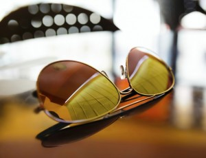 골드빛 선글라스가 유리테이블 위에 놓여져 있다.