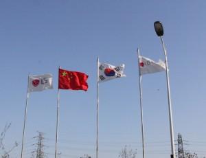 푸른 하늘 배경에 LG화학 깃발이 양쪽에 있고 중앙 좌측에 중국 국기가, 우측에 태극기가 휘날리고 있다.