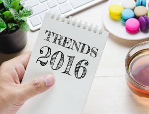 TRENDS 2016이라 쓰여진 수첩을 손에 들고 있고, 그 주변으로 작은 화분과 하얀색키보드, 흰접시에 담긴 알록달록한 마카롱, 투명잔에 홍차가 담겨있다.