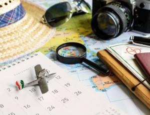 달력과, 모형 비행기, 돋보기, 지도, 여권, 카메라, 선글라스, 모자가 흐트러져 있다.