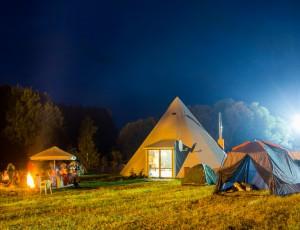 어두운 밤 캠핑장 속 텐트 3개가 보이고 텐트 안에서 환한 불빛이 새어나오고 있다.