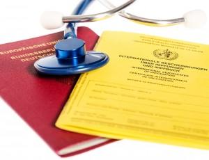 붉은색 노란색 여권 위에 청진기가 놓여 있다.