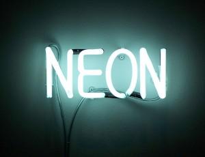 'NEON'이라는 문구의 네온사인이 벽에 설치되어 있다.