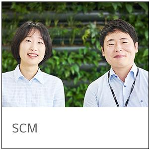 SCM 남녀 직원 두 분이 미소를 짓고 나란히 서있다.
