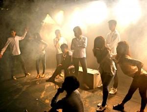 어두운 공간에서 많은 사람들이 각자의 포즈를 취하며 뮤지컬을 하고 있다.