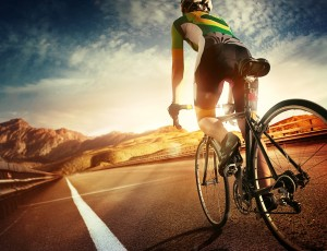 자전거 안전장비를 착용한 사람이 자전거를 타고 길을 달리고 있다.