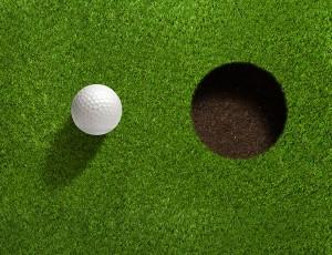 골프 잔디에 홀 옆에 골프공이 있다.
