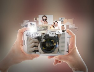 스마트폰을 양손으로 들고 여러장의 사진을 편집하고 있다.