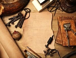 가죽과 가죽제품을 만들 때 필요한 도구들이 책상 위에 놓여있다.