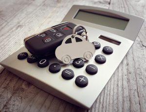 계산기 위에 자동차 키가 놓여있다.
