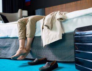 신발을 벗은 채로 침대 위에 누워있는 남자의 다리가 보인다.