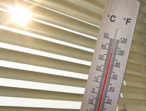 창문에 블라이드 사이로 햇볕이 들어오고 온도계 눈금이 38도로 되어 있다.