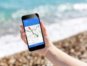 바닷가에서 휴대전화로 길을 확인하고 있는 사진