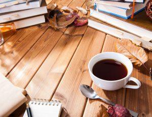 나무 바닥에 커피와 책이 함께 놓여있다.