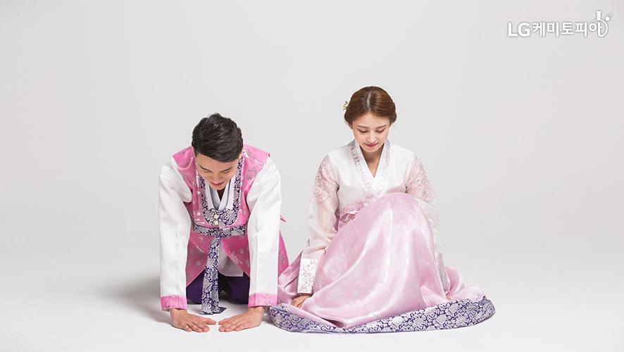 한복을 입은 남녀가 나란히 앉아 절을 하고 있다.