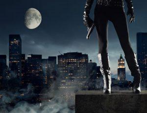 달이 떠있는 밤에 건물 옥상에 총을 든 사람이 서있다.