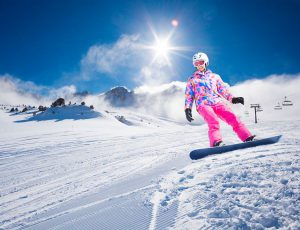 한 여자가 눈 덮인 산에서 스노우 보드를 타고 내려오고 있다