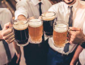 정장을 입은 남자들이 맥주잔으로 건배를 하고 있다.