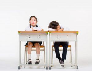 남자아이는 책상에 엎드려 있고, 여자 아이는 책상에 앉아 눈을 감고 있다.
