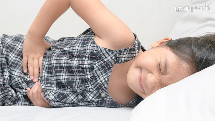 여자아이가 침대에 누워서 두 손으로 배를 움켜잡고 있다.