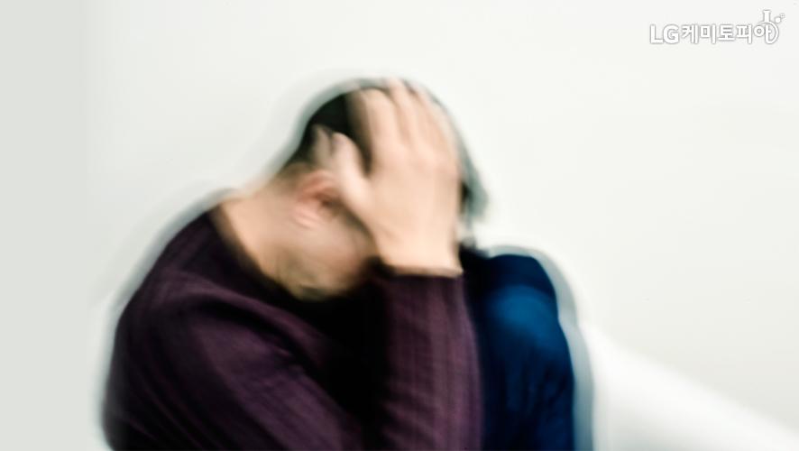 남자가 두 손으로 머리를 감싸고 벽에 기대 앉아있다.