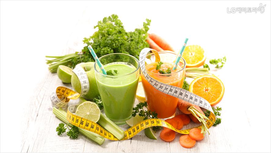 채소와 과일 가운데 디톡스 쥬스 두 잔.