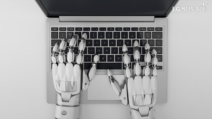 로봇 손으로 노트북 키보드를 치고 있다.