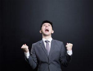 정장을 입은 남자가 두 주먹을 쥐고 허공에 소리를 지르고 있다.