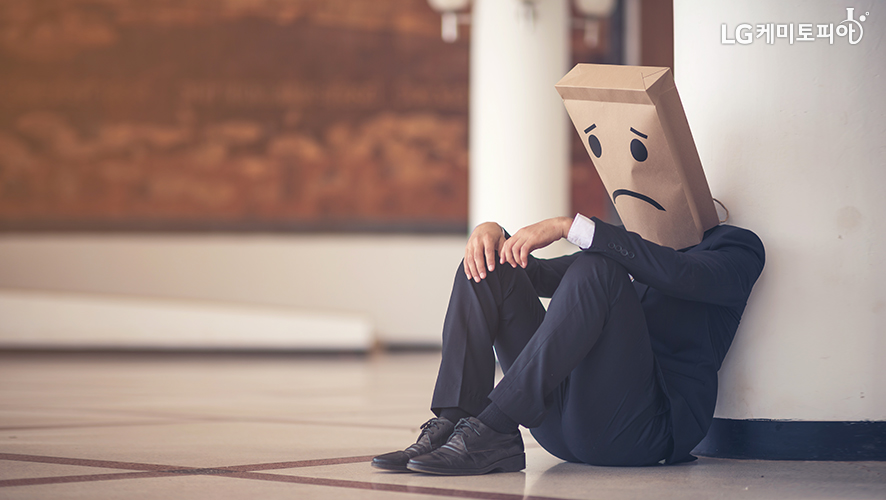 울상을 하고 있는 사람이 바닥에 앉아있다.