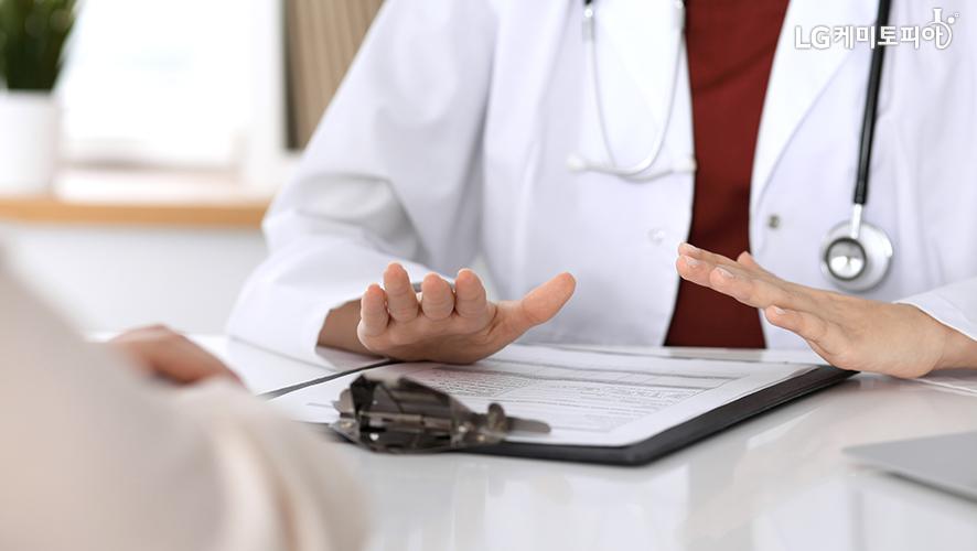 목에 청진기를 두르고 흰색 가운을 입은 의사가 진료차트를 보고 환자와 상담을 하고 있다.