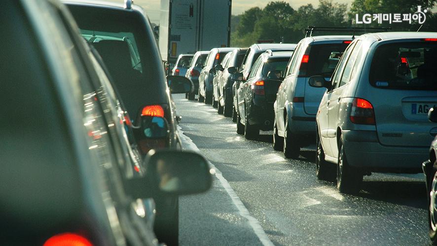도로에 차들이 줄지어 서 있다.
