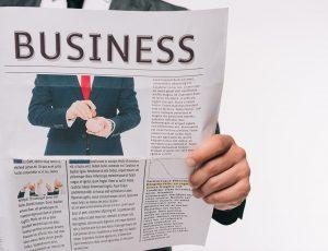 정장을 입은 남자가 신문을 펼쳐 들고 있다.