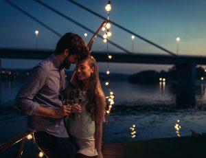 남자와 여자 커플이 서서 샴페인을 마시고 있다.