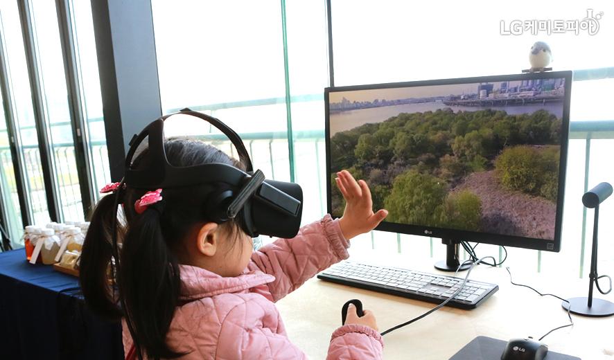 여자아이가 VR체험을 하고 있다.