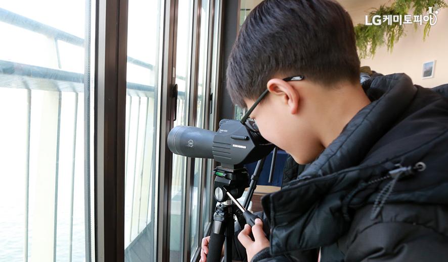 남자아이가 망원경으로 밖을 보고있다.